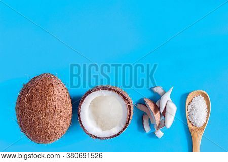 Brown Coconut, Half Of Nut, Pieces And Shavings In Spoon Are On Bottom Of Blue Background. Tropical