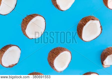 Brown Halves Of Coconut Nuts Are Scattered On Blue Background. Tropical Palm Fruit. Organic Natural