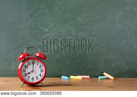 Back To School Or Education Template With Alarm Clock And Colorful Chalks Against Empty Blackboard B