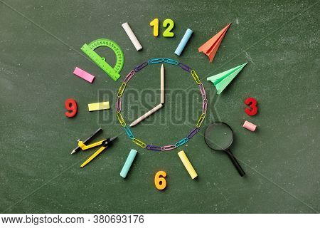 Creative Clock Face From Colorful School Supplies On Blackboard Top View And Flat Lay. Back To Schoo