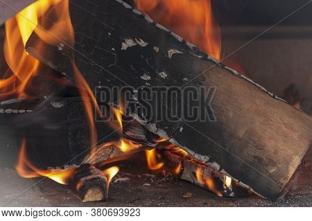 A Close Up View Of Fire Wood That Has Been Lit Under A Pizza Oven