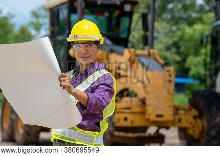 Engineer Or Architect Women Holding Blueprints With Loader Truck At Construction Site,engineering Co