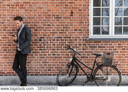 Young businessman going to work on bike commute using his mobile cellphone against city brick wall background. Happy business man bicycle commuter arriving at office using phone texting.