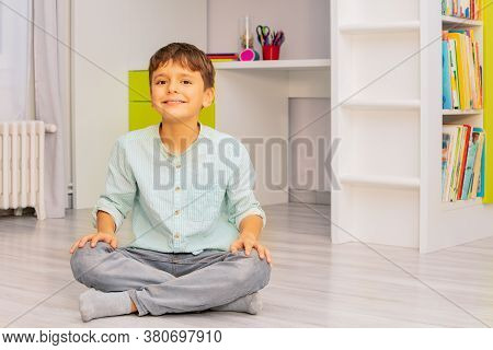 Smiling Calm Little Boy Sit In His Room With Positive Expression