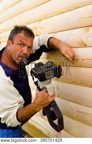 A Man Hammers Nails With A Camera. Portrait And Humor.