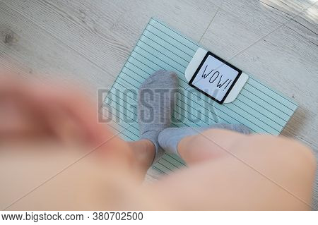 Top View Of Female Legs In Gray Socks On Electronic Scales. The Inscription On The Display Is Wow.