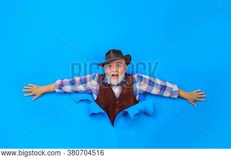 Bearded Man In Cowboy Hat Looking Through Paper. Portrait Of Bearded Man Wearing Cowboy Hat. Cowboy