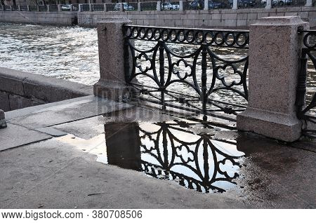 The Pattern Of The Lattice Is Reflected In The Puddle After The Rain.