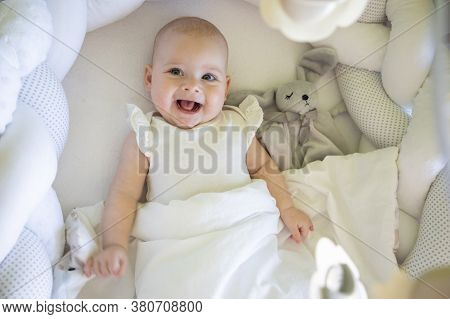 Adorable Smiling Baby Girl With A Toy Bunny In Cot In Home Bedroom