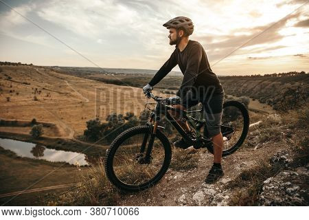 Full Body Man In Helmet Sitting On Bicycle And Admiring Mountainous Terrain During Sunset In Nature