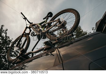 From Below Bicycle Mounted On Rack On Roof Of Contemporary Van In Countryside