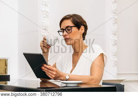 Mid Adult Woman Holding A Cup And Looking On Digital Tablet. Businesswoman Reading While Having Brea