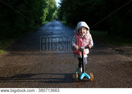 Pretty Cheerful Toddler Girl Riding Scooter In The Coutryside