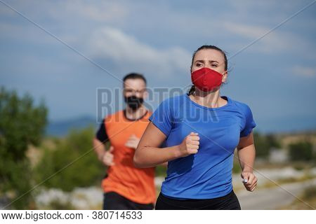 Couple running in nature at morning wearing protective face masks