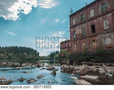 Abandoned Factory On The Water Edge. Old Building On The Rocky River. Brown Brick Wall. Water Stream