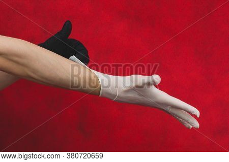 Hand In The Black Glove Puts The White Glove On The Other. Person Puts On Medical Gloves On A Red Ba