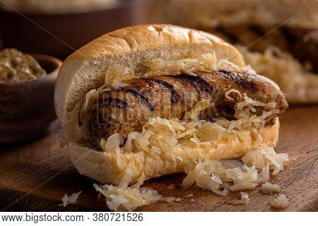 Closeup Of Grilled Bratwurst With Sauerkraut On A Bun On A Wooden Board