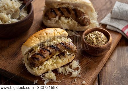 Grilled Bratwurst With Sauerkraut On A Bun And Mustard In A Bowl On A Wooden Board
