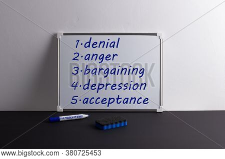 Whiteboard On Black Table With Words: Denial, Anger, Bargaining, Depression, Acceptance. Marker With