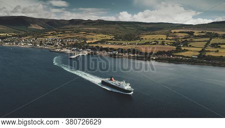 Scotland, Brodick Ferry Terminus aerial panoramic shot of ship crossing, Arran Island. Beautiful passenger ferry go from harbor at Firth-of-Clyde Gulf to mainland. Cinematic scenery view