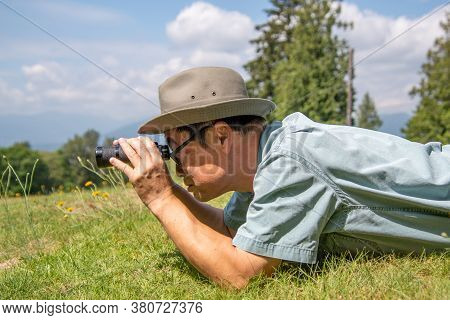 A Side-view Of A Man Lying Down On A Grass Field And Using Binoculars.    Vancouver Bc Canada