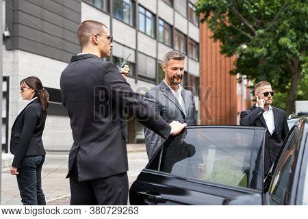 Bodyguards Protecting Businessman Opening Car Vehicle Door