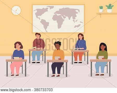 Kids Sitting At Their Desk With Books In Classroom With World Map And Clock On The Wall. Interior Of