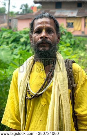 An Indian Wanderer Monk In A Traditional Yellow Dress Stands In A Special Posture.