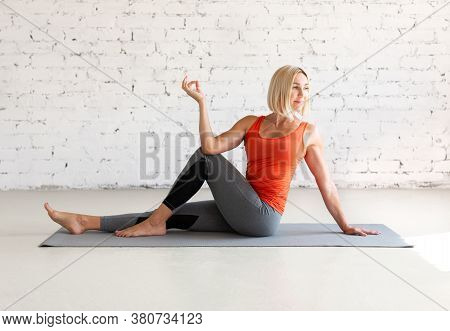 Attractive Caucasian Woman Practice Hatha Yoga Indoor In Loft White Studio. Seated Side Twist Pose,