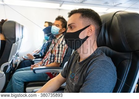 Airplane Passengers Are Wearing Medical Masks On Their Faces. Air Travel During The Coronavirus Pand
