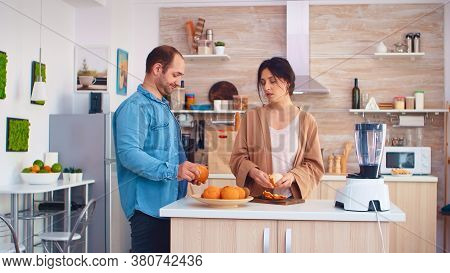 Woman Peeling Off Oranges For Nutritious Smoothie In Kitchen. Husband Wearing Denim Shirt. Cheerful