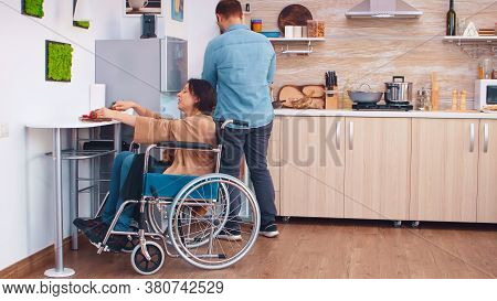 Woman With Legs Paralysis In Wheelchair Cutting Red Pepper On Slicing Board. Woman With Paralysis Ha