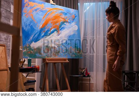Artist Woman Checking Her Abstract Painting In Art Workshop. Modern Artwork Paint On Canvas, Creativ