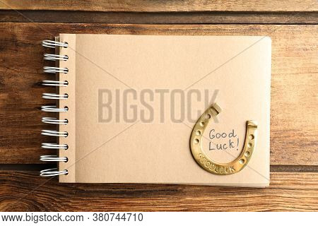 Notebook With Phrase Good Luck And Horseshoe On Wooden Table, Top View. Space For Text
