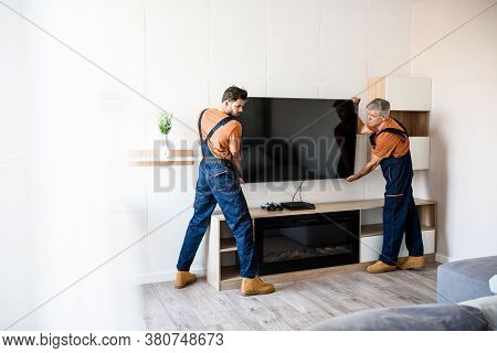 Two Handymen, Workers In Uniform Hanging, Installing Tv Television On The Wall Indoors. Repair And A