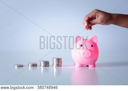 Hand Of Kid Holding Coin Put In Piggy Bank With Money Stack Growing Growth Saving Money, Concept Inv