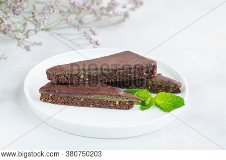 Pieces Of Chocolate Tart With Nuts And Mint Filling On A Concrete Plate On A White Background. Close