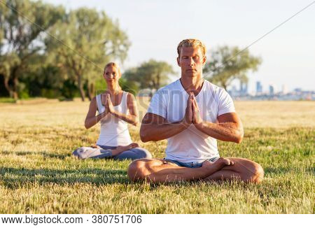 Fit man and beautiful woman practicing yoga outdoor on the grass. Stretching exercise in the sunset. Sport, fitness, health care and lifestyle concepts.