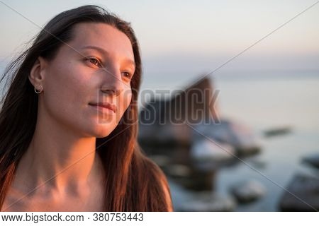 Beautiful young brunette looking away and dreaming while resting near sea during sunset