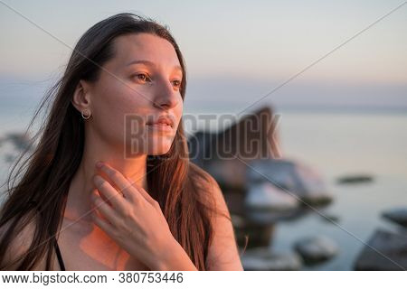 Dreamy young female with long hair touching neck and looking away on blurred background of sea and sunset sky