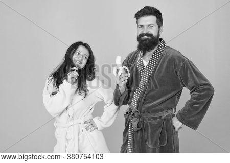 Healthy Food. Couple Sleepy Faces Domestic Clothes Eat Banana. Couple In Love Bathrobes. Advice Rela