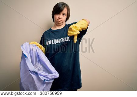 Young down syndrome volunteer woman picking rubbish and plastic from the trash with angry face, negative sign showing dislike with thumbs down, rejection concept