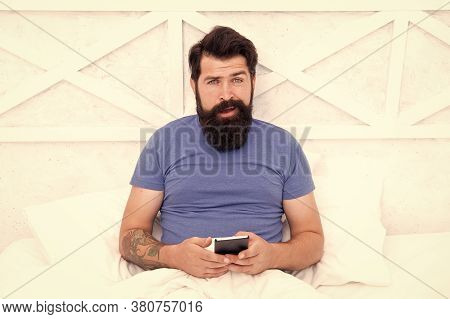 Checking Social Networks. Cellular Communication. Modern Guy Talking On Smartphone In Bed. Handsome