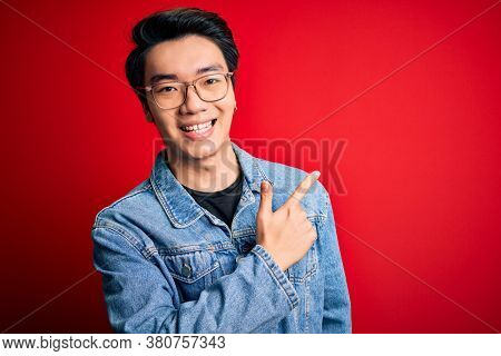 Young handsome chinese man wearing denim jacket and glasses over red background cheerful with a smile of face pointing with hand and finger up to the side with happy and natural expression on face