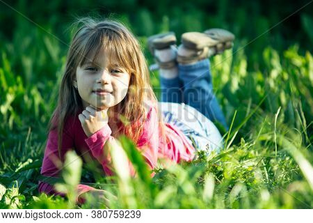 Portrait of little girl lying on a meadow in the grass.