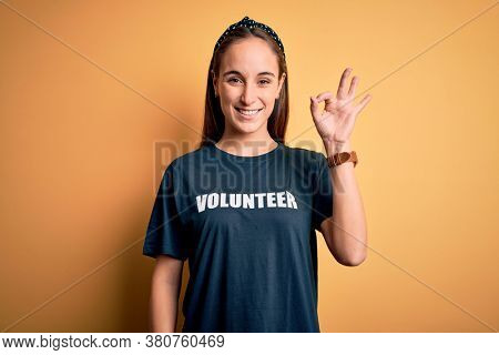 Young beautiful woman wearing volunteer t-shirt doing volunteering over yellow background smiling positive doing ok sign with hand and fingers. Successful expression.
