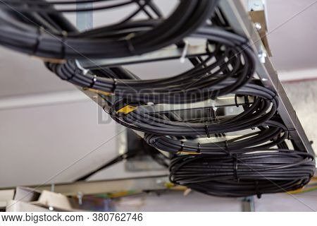Cable Management. Working Wires, Black Cables Wound Into A Coil, A Circle. Rings Of Coiled Wires, Wi
