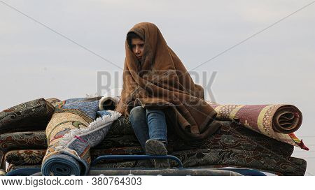 Aleppo, Syria 17 February 2018:\na Child Fleeing The Bombing Sits On Top Of The Car And Wears A Thic