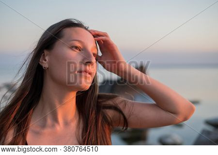 Pretty young woman touching long hair and dreaming while looking away near sea during sundown