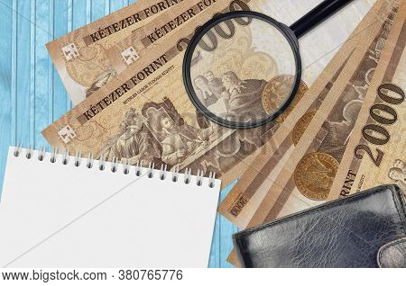 2000 Hungarian Forint Bills And Magnifying Glass With Black Purse And Notepad. Concept Of Counterfei